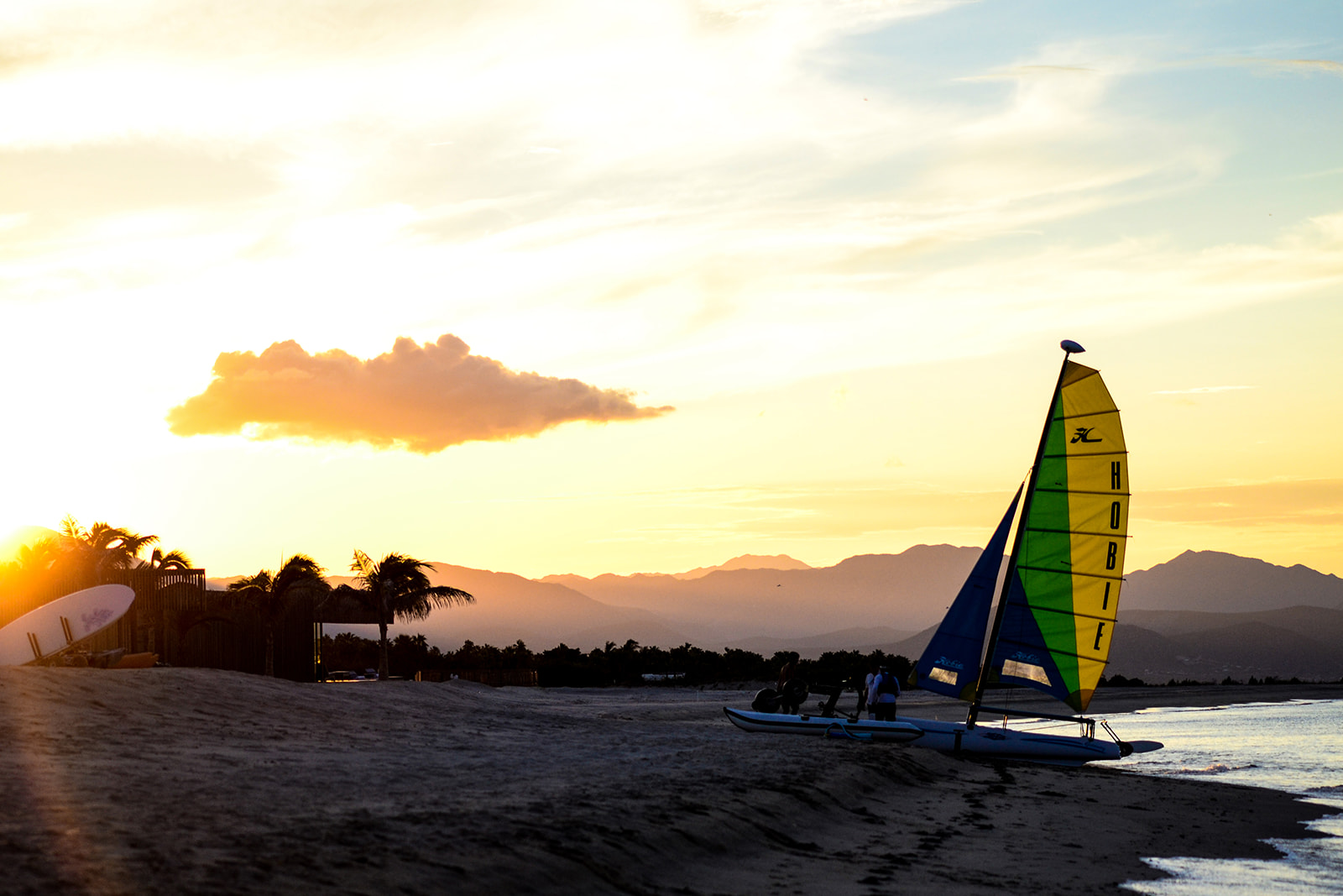 Beach at sunset with sailboat